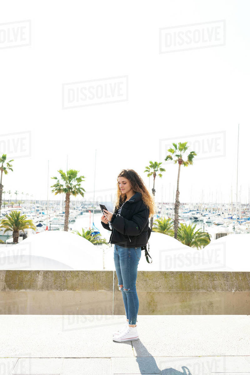 Young student woman looking at her smartphone by the sea port Royalty-free stock photo