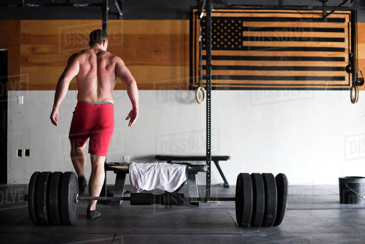 A weightlifter prepares to deadlift at a gym. Royalty-free stock photo