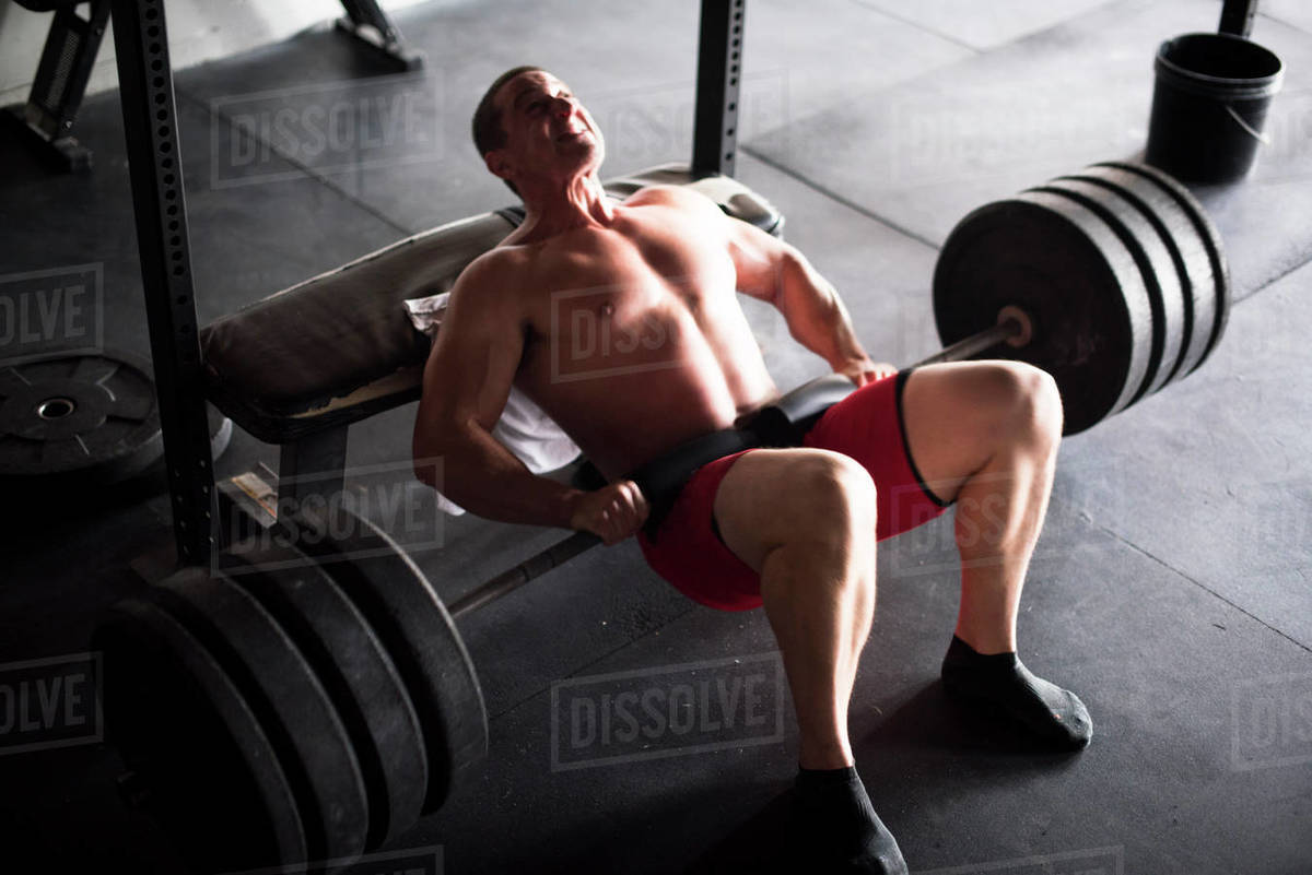 An athlete doing weighted hip thrusts at a gym in San Diego, CA. Royalty-free stock photo