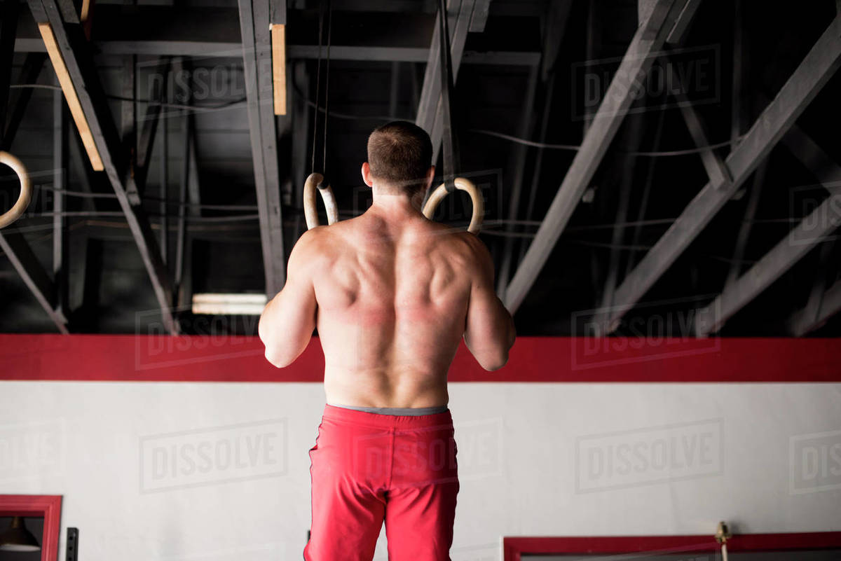 An athlete doing ring pull-ups at a gym. Royalty-free stock photo