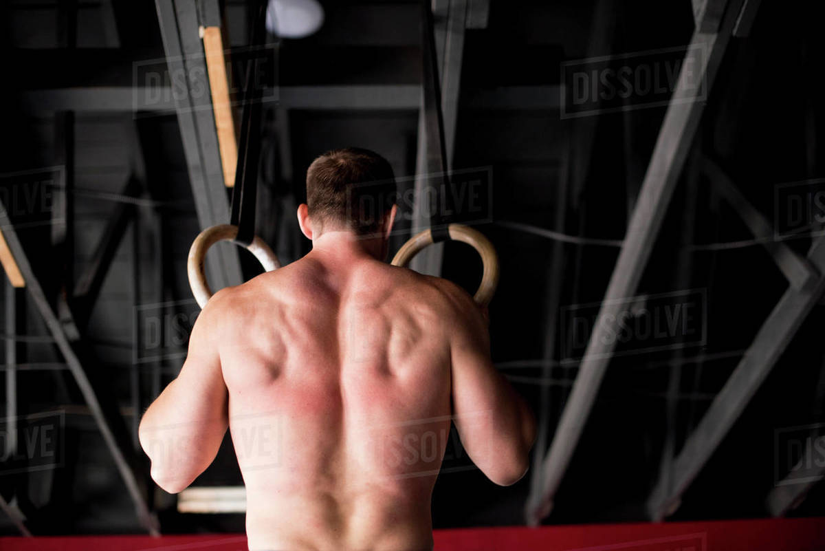 An athlete doing ring pull-ups at a warehouse gym. Royalty-free stock photo