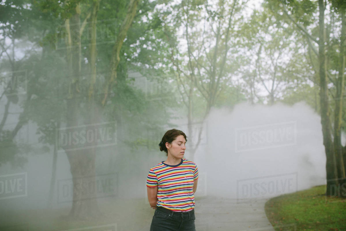 Young woman with downcast eyes standing on a path in a foggy park Royalty-free stock photo