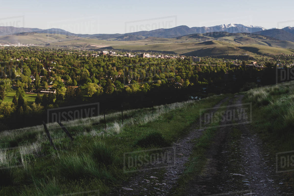 A dirt road leads to Missoula, Montana in spring with Snowbowl behind Royalty-free stock photo