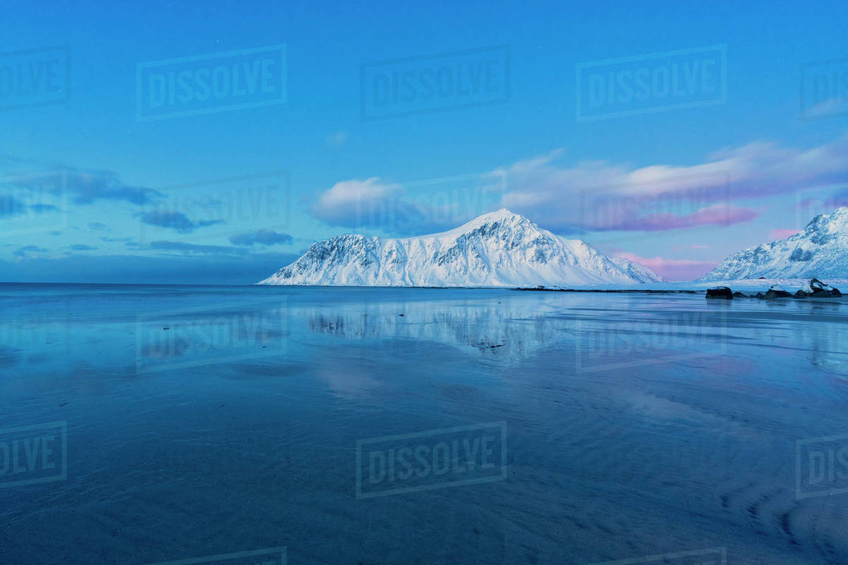 Snowy peaks mirrored in the cold sea, Skagsanden beach, Norway Royalty-free stock photo