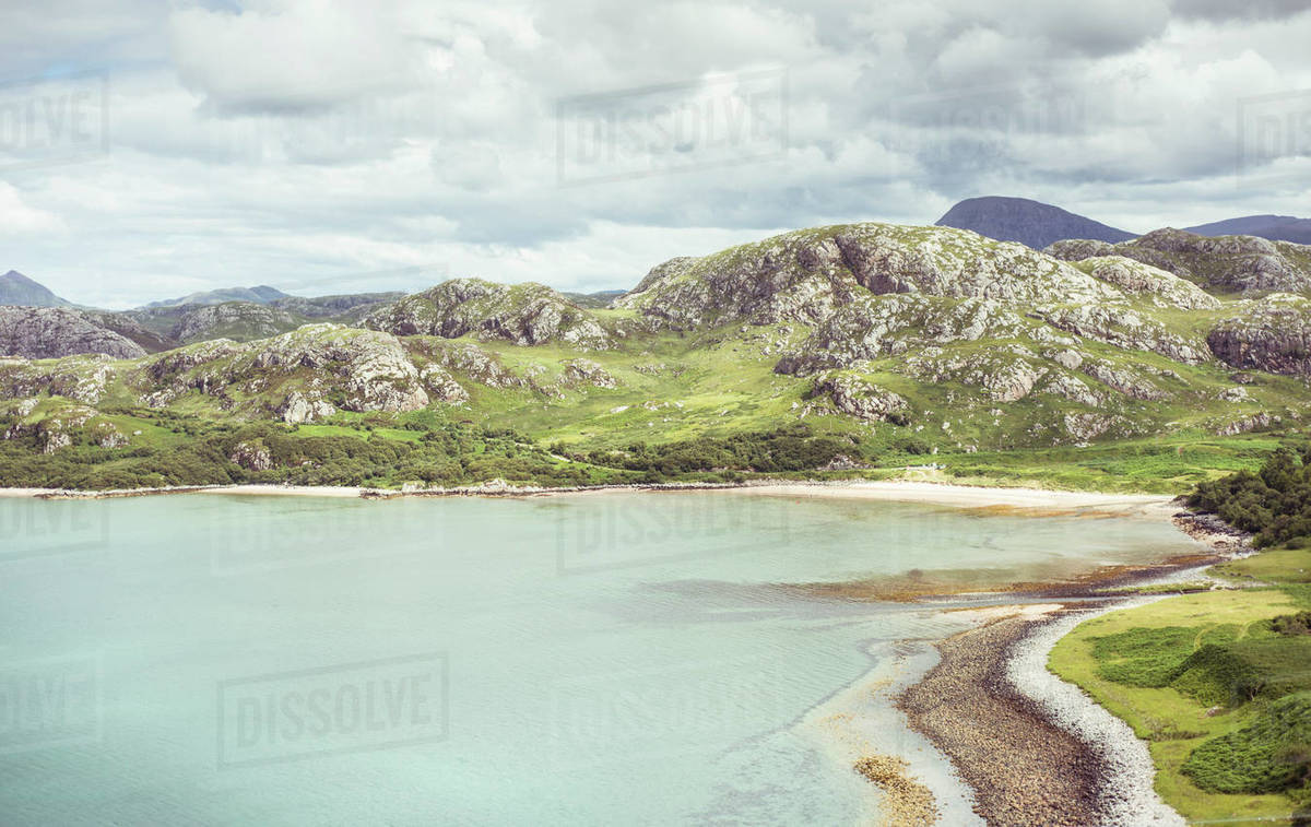 Beautiful blue ocean and round rocky mountains coast in Scotland Royalty-free stock photo