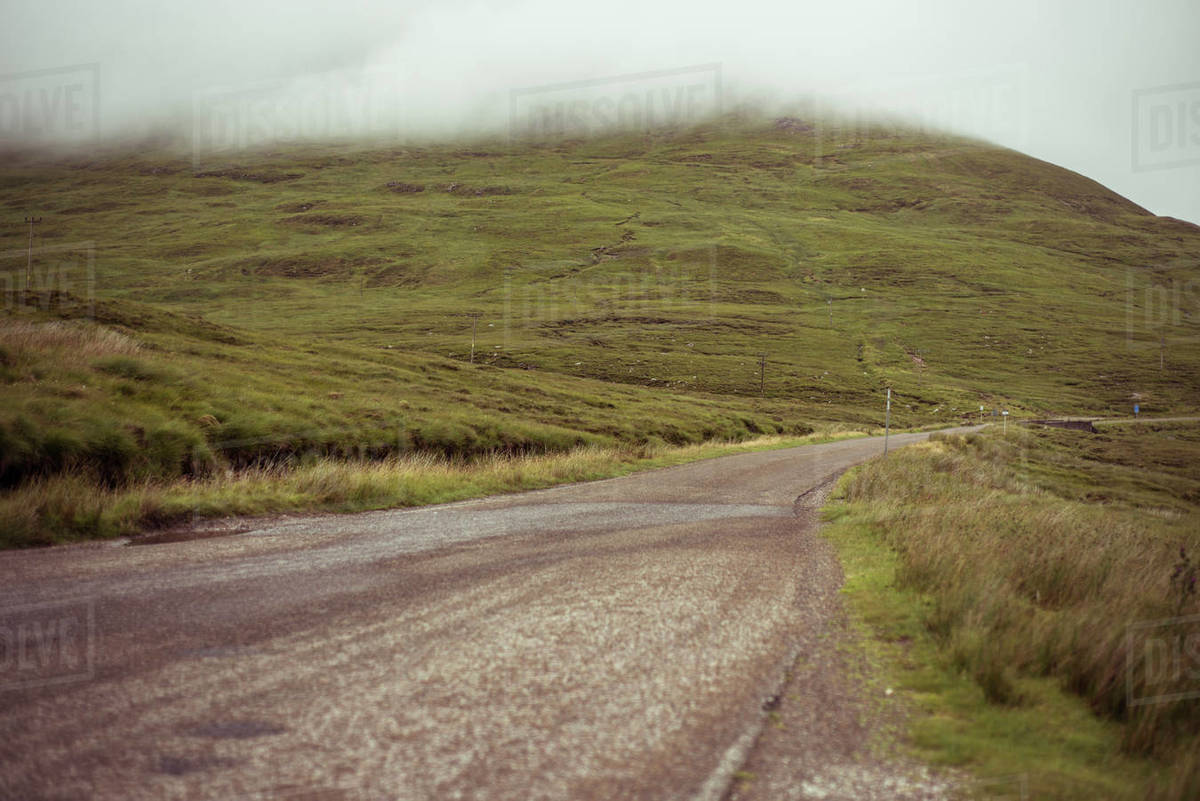 Road through Misty moody landscape of remote mountains in scotland Royalty-free stock photo