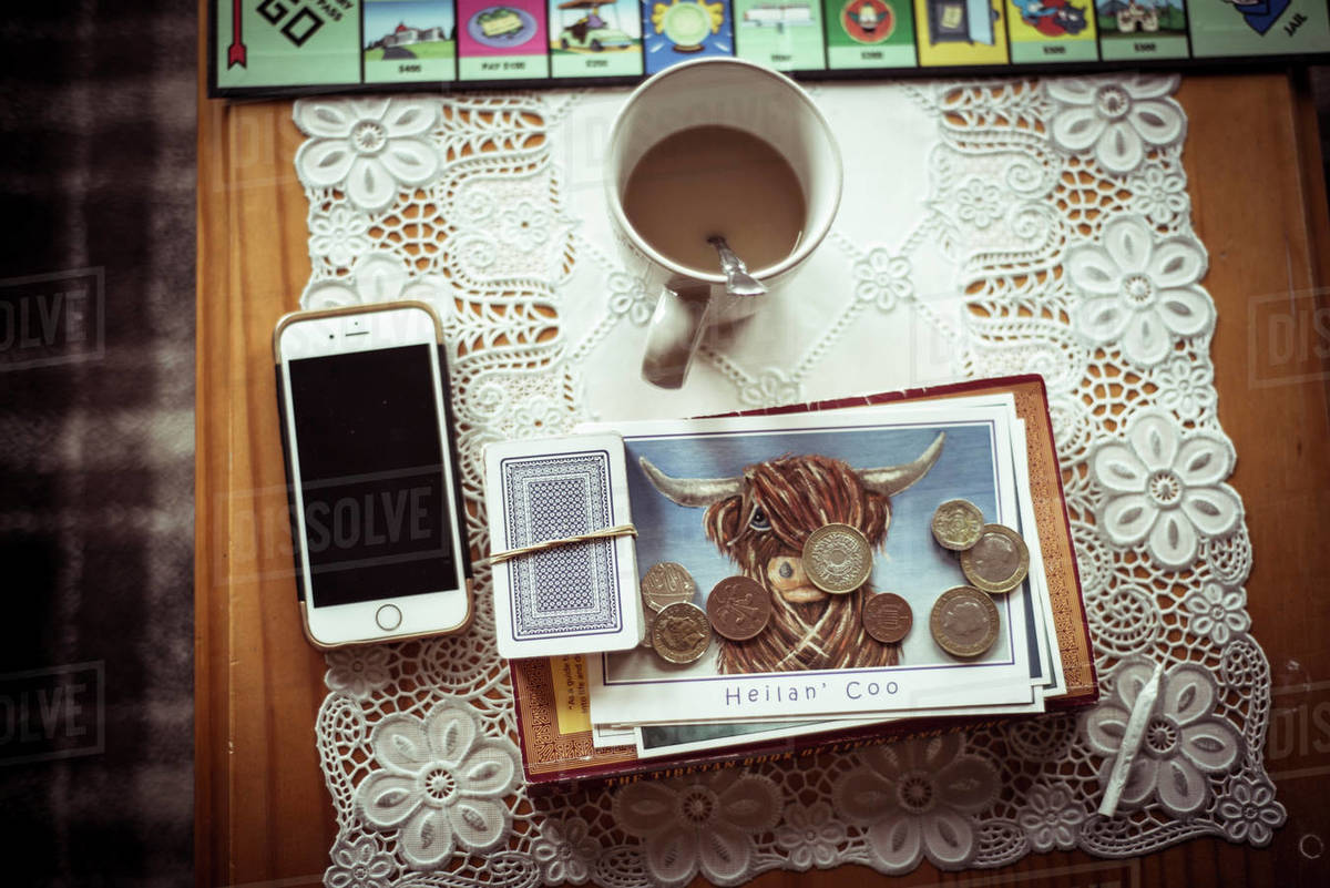 Highland cow postcard with coins and tea and phone on table Royalty-free stock photo