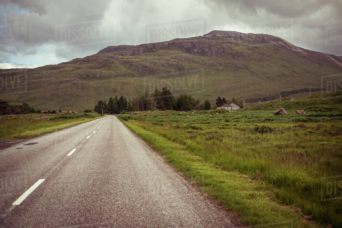 Remote empty road leads to moody mountain Royalty-free stock photo