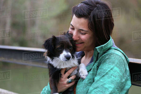 Happy woman embracing Border Collie while sitting on bench in park Royalty-free stock photo