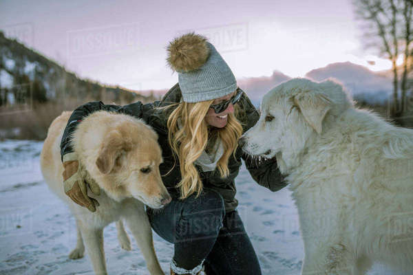 Happy woman stroking dogs while crouching on snowy field against sky during sunset Royalty-free stock photo