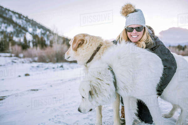 Happy woman embracing dogs on snowy field during sunset Royalty-free stock photo