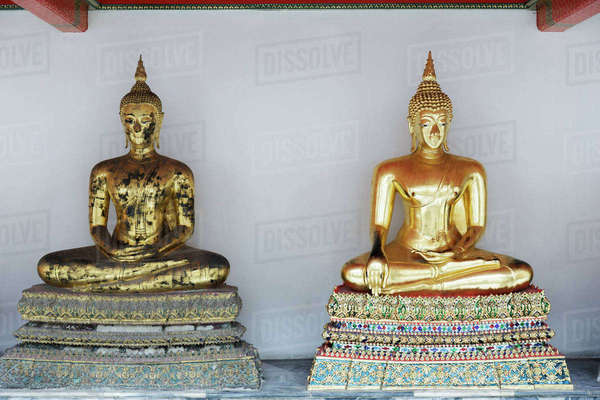 Golden Buddha statues against wall in temple Royalty-free stock photo