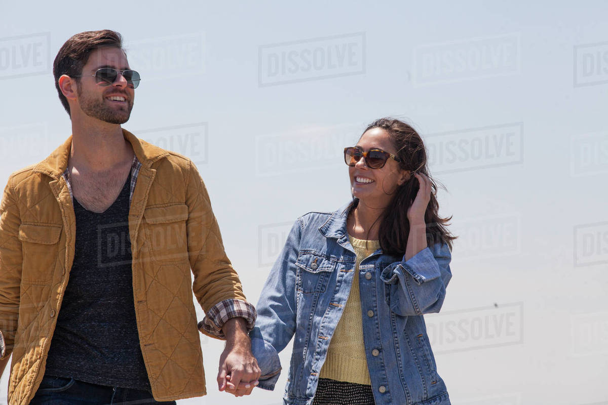 Happy couple holding hands while standing against clear sky on sunny day Royalty-free stock photo