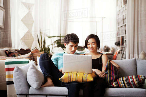 Young couple using laptop while sitting on sofa at home Royalty-free stock photo