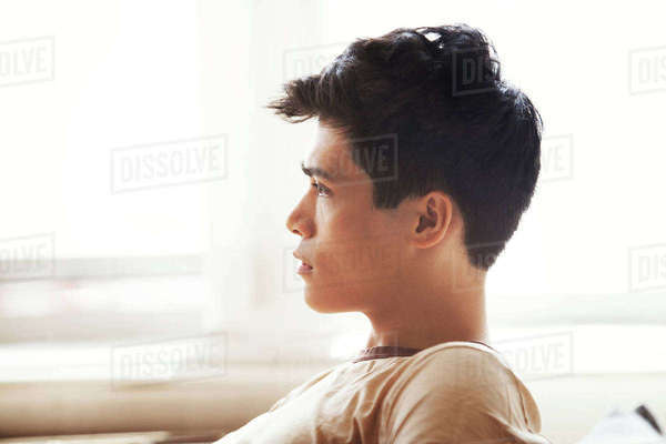 Side view of thoughtful man sitting by window at home Royalty-free stock photo