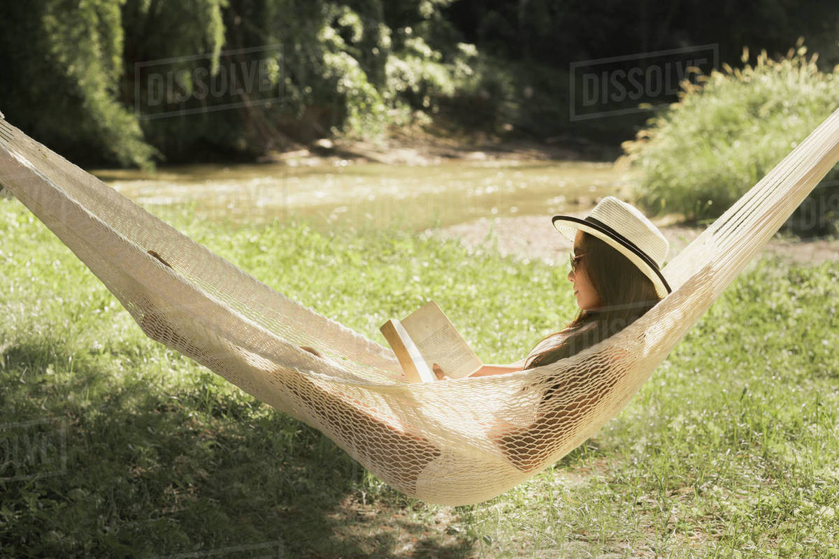 Woman reading book while relaxing on hammock in park - Stock Photo -  Dissolve