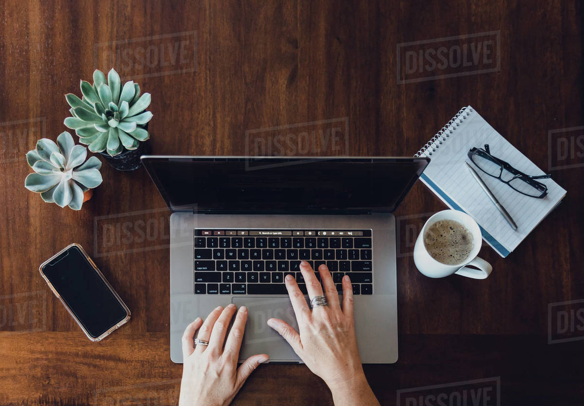 Overhead view of woman's hands working on laptop at wooden table. Royalty-free stock photo