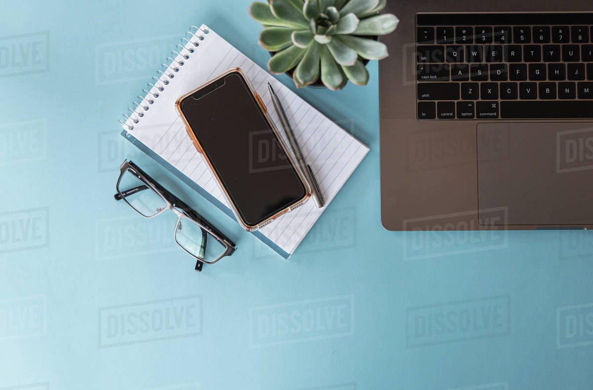 Overhead view of workspace with laptop, phone, glasses and notepad. Royalty-free stock photo