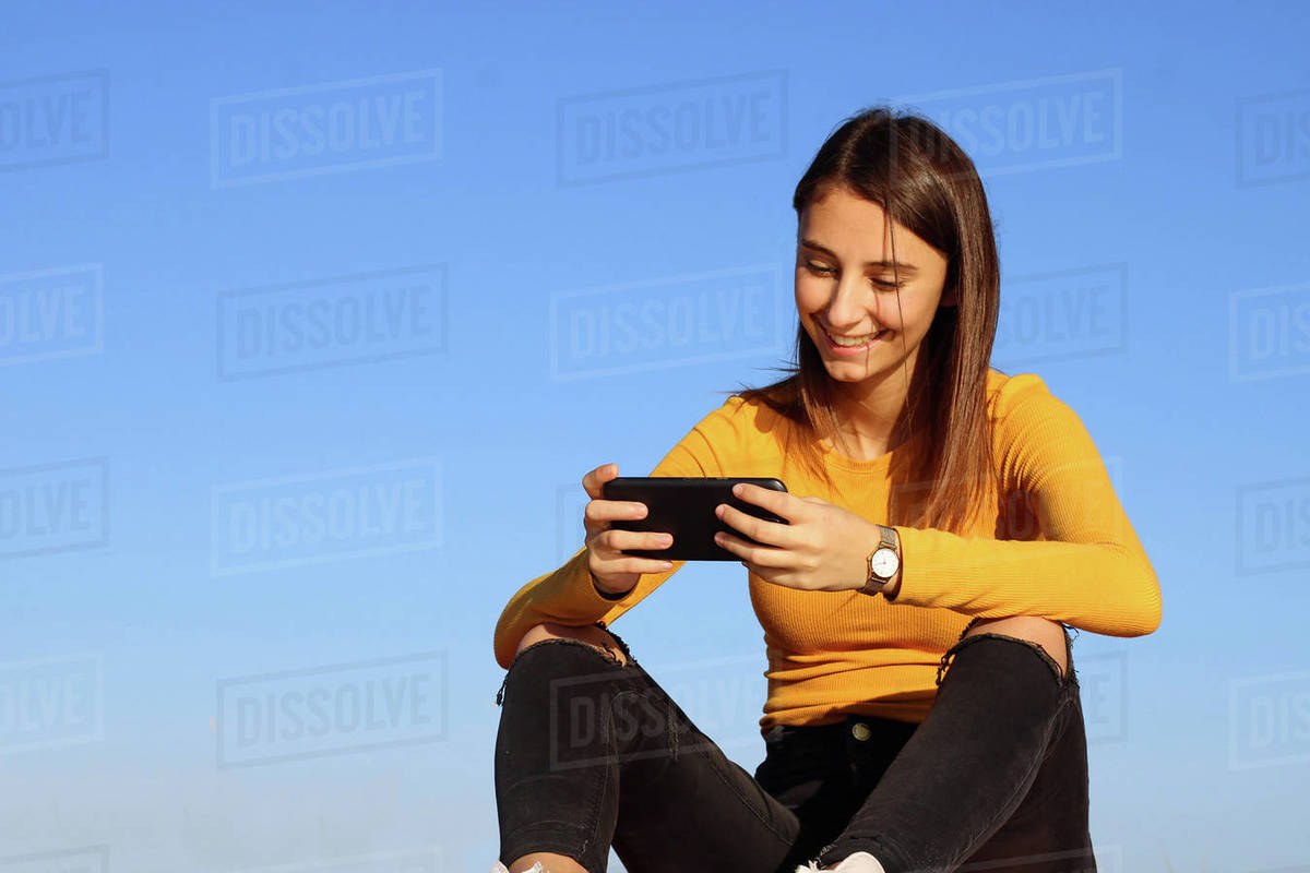 Young and beautiful girl playing a game on her cell phone. Royalty-free stock photo