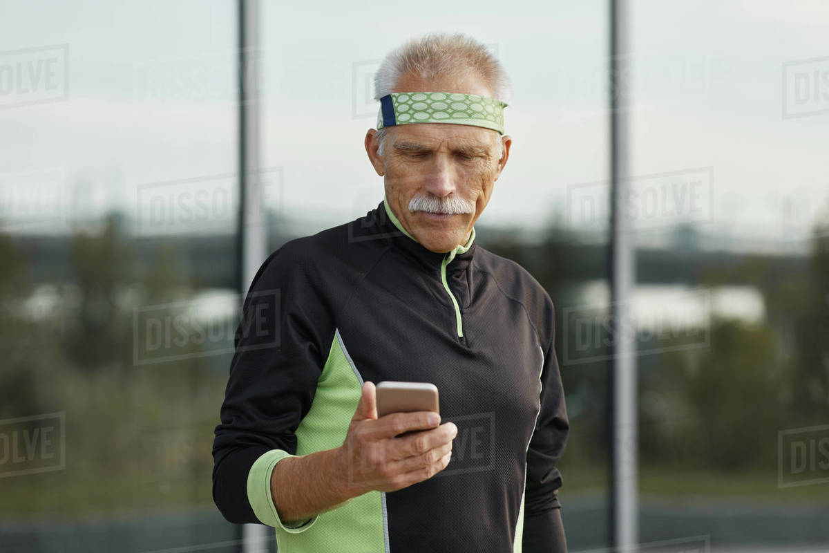 Handsome Sporty Senior Man Using Smartphone Royalty-free stock photo