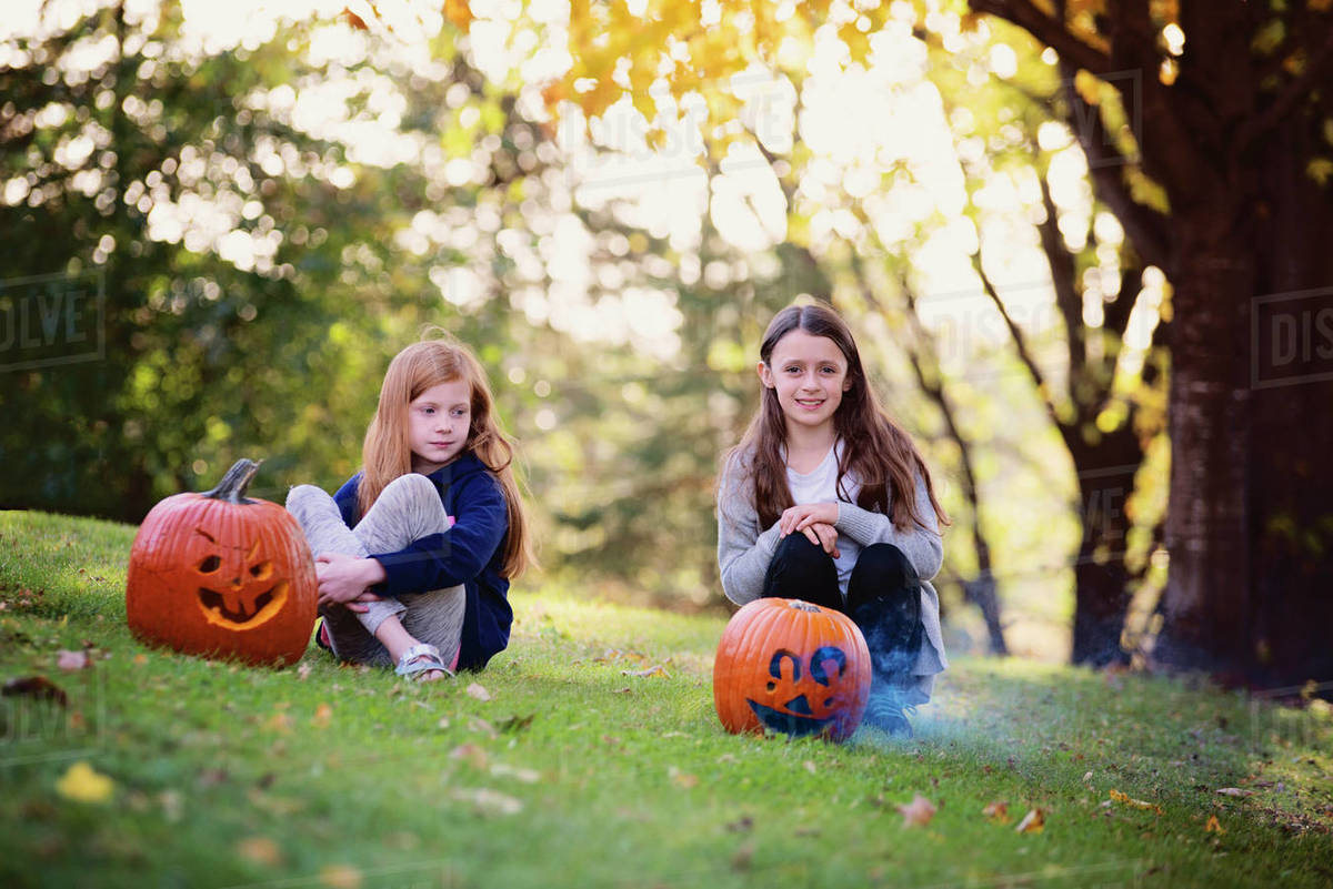 Two Young Girls Sitting Outside by Smoking Pumpkins in the Fall Royalty-free stock photo