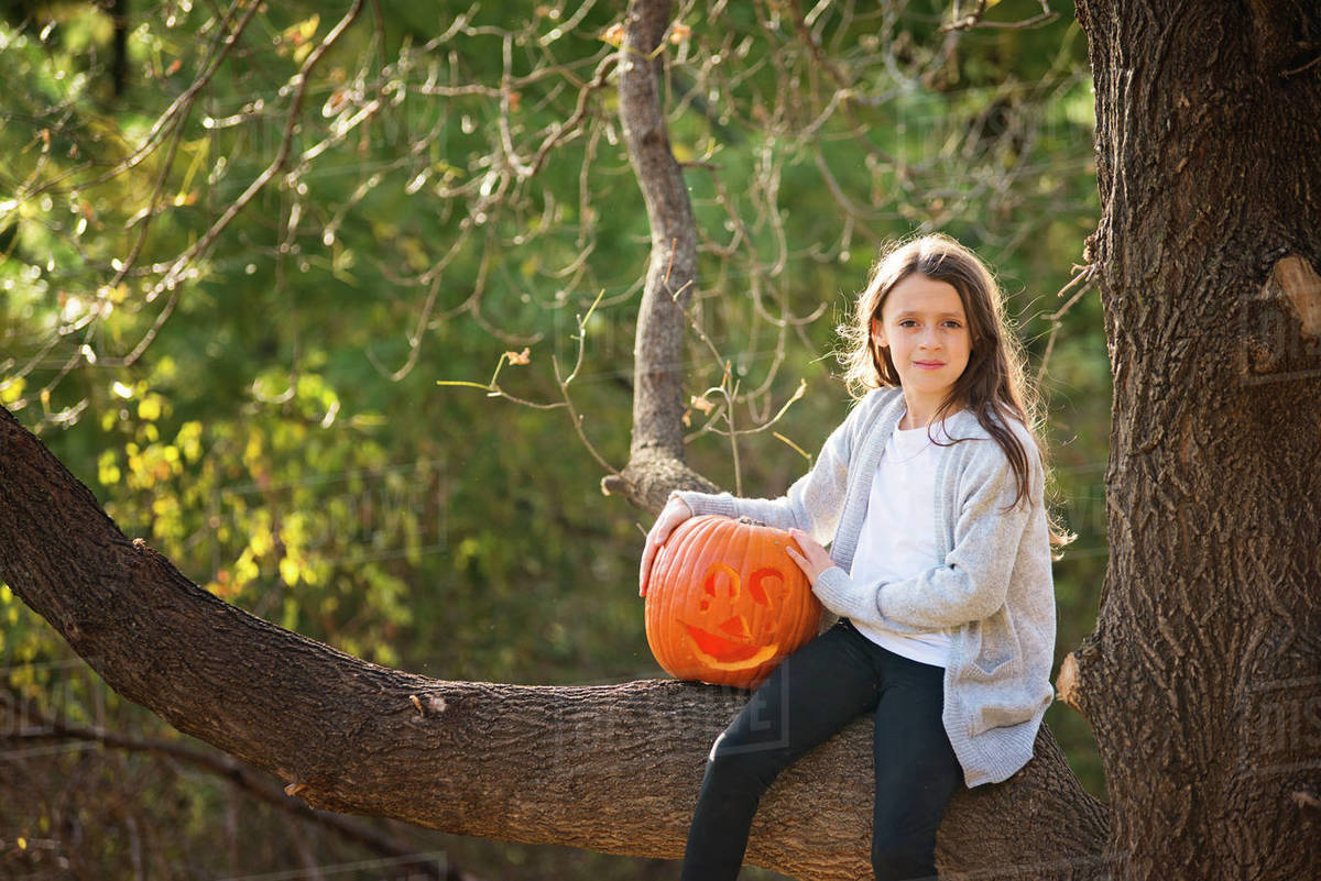 Young Girl Sitting in Tree with Carved Pumpkin Royalty-free stock photo