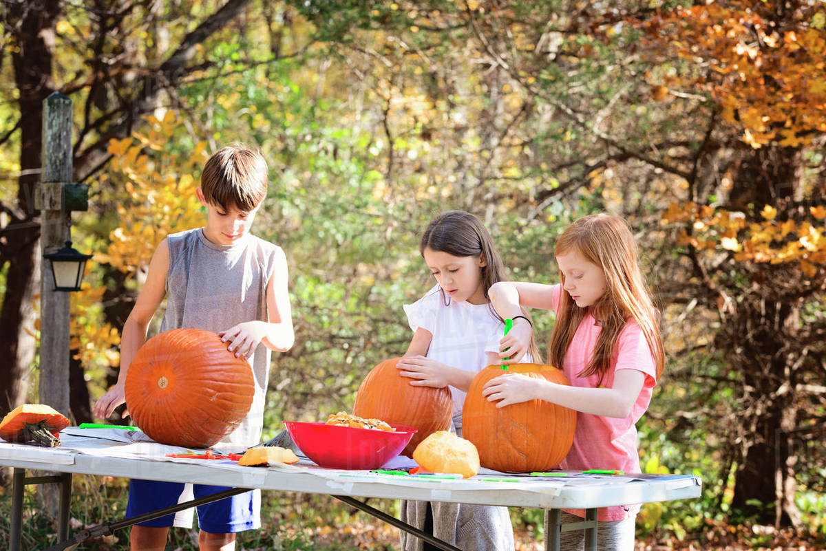 Three Young Children Carving Pumpkins Outdoors Royalty-free stock photo