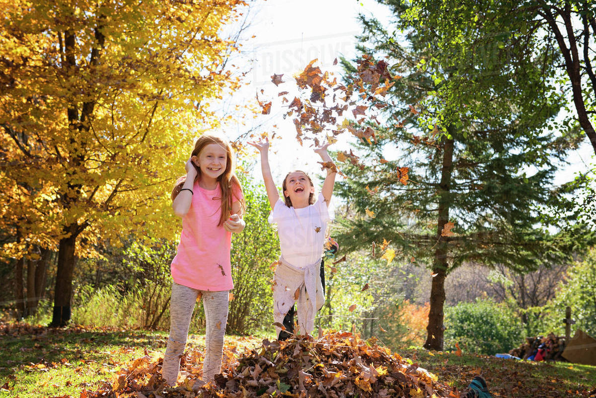 Two Young Girls Playing in Fall Leaves Royalty-free stock photo
