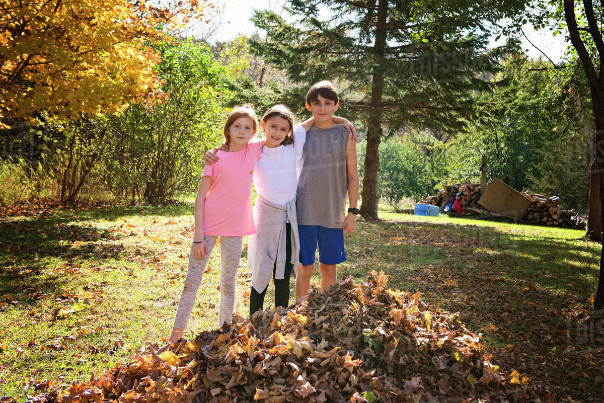 Three Young Friends Outdoors by Leaf Pile Royalty-free stock photo