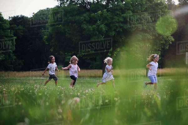 Friends running on grassy field at park Royalty-free stock photo