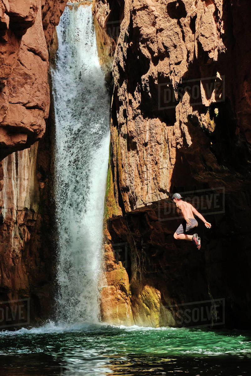 A hiker takes the plunge at Cibeque Falls on Cibeque Creek in Arizona Royalty-free stock photo