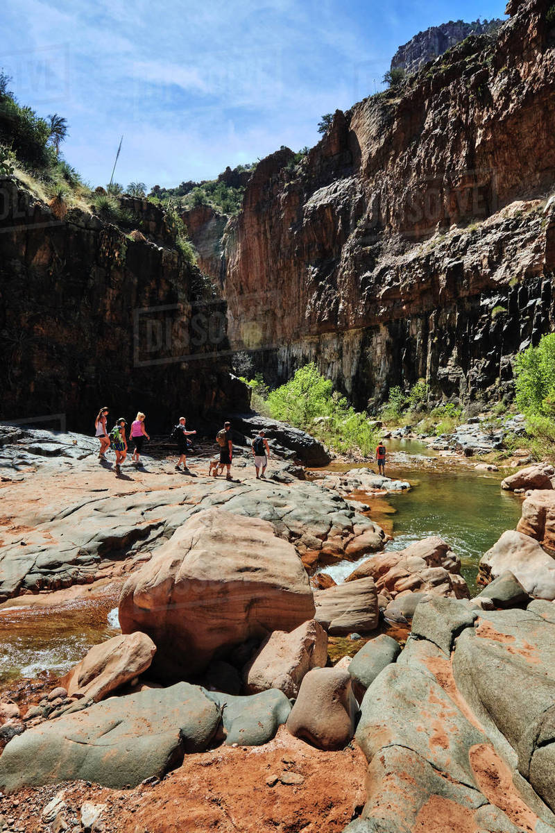 Hikers making their way past a pool on Cibeque Creek, in Arizona Royalty-free stock photo