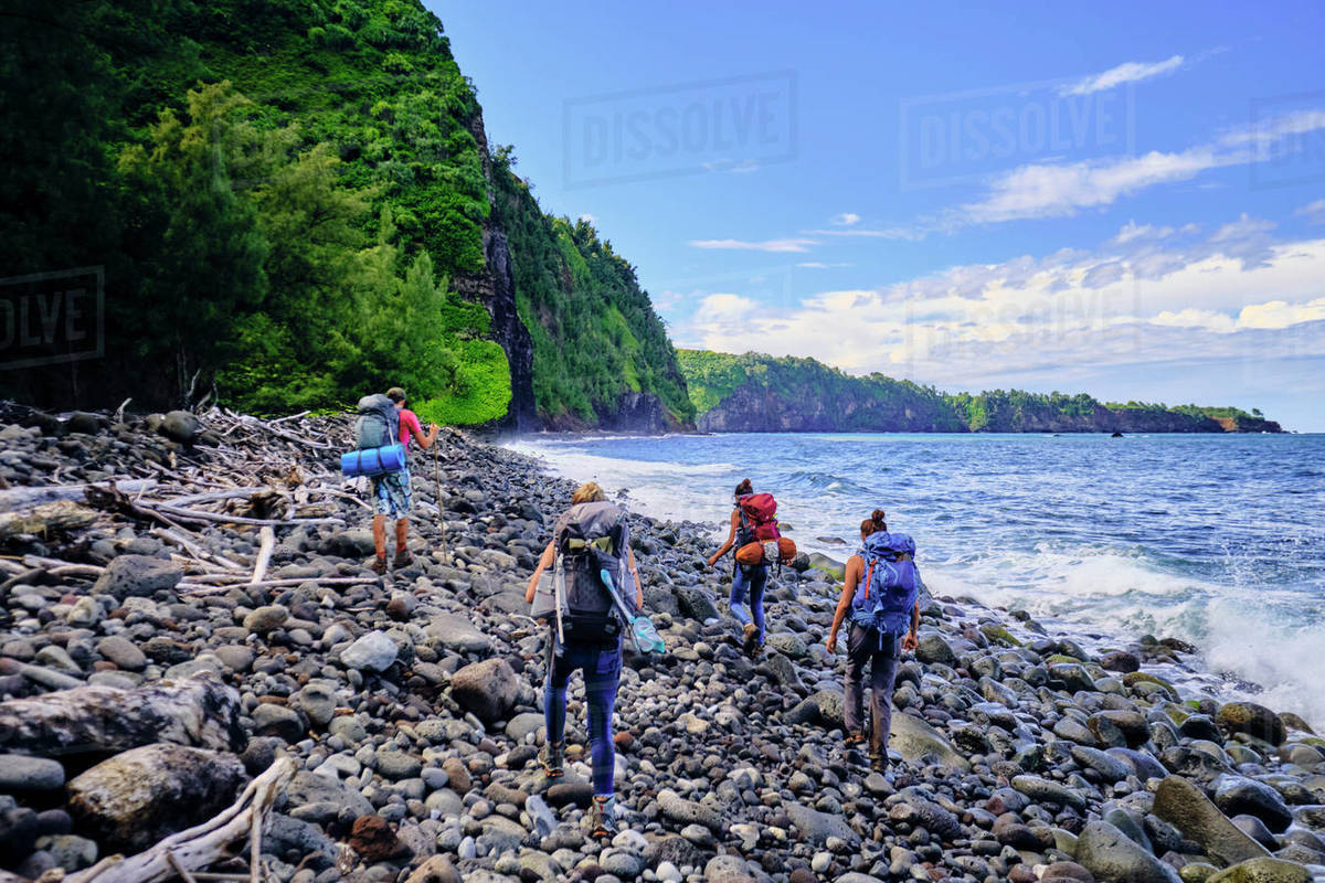 A group of backpackers hikes along the Pololu coast of Hawaii Royalty-free stock photo