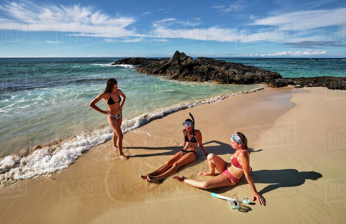 Three friends enjoying the waves and sand on Makalawena Beach, Hawaii Royalty-free stock photo