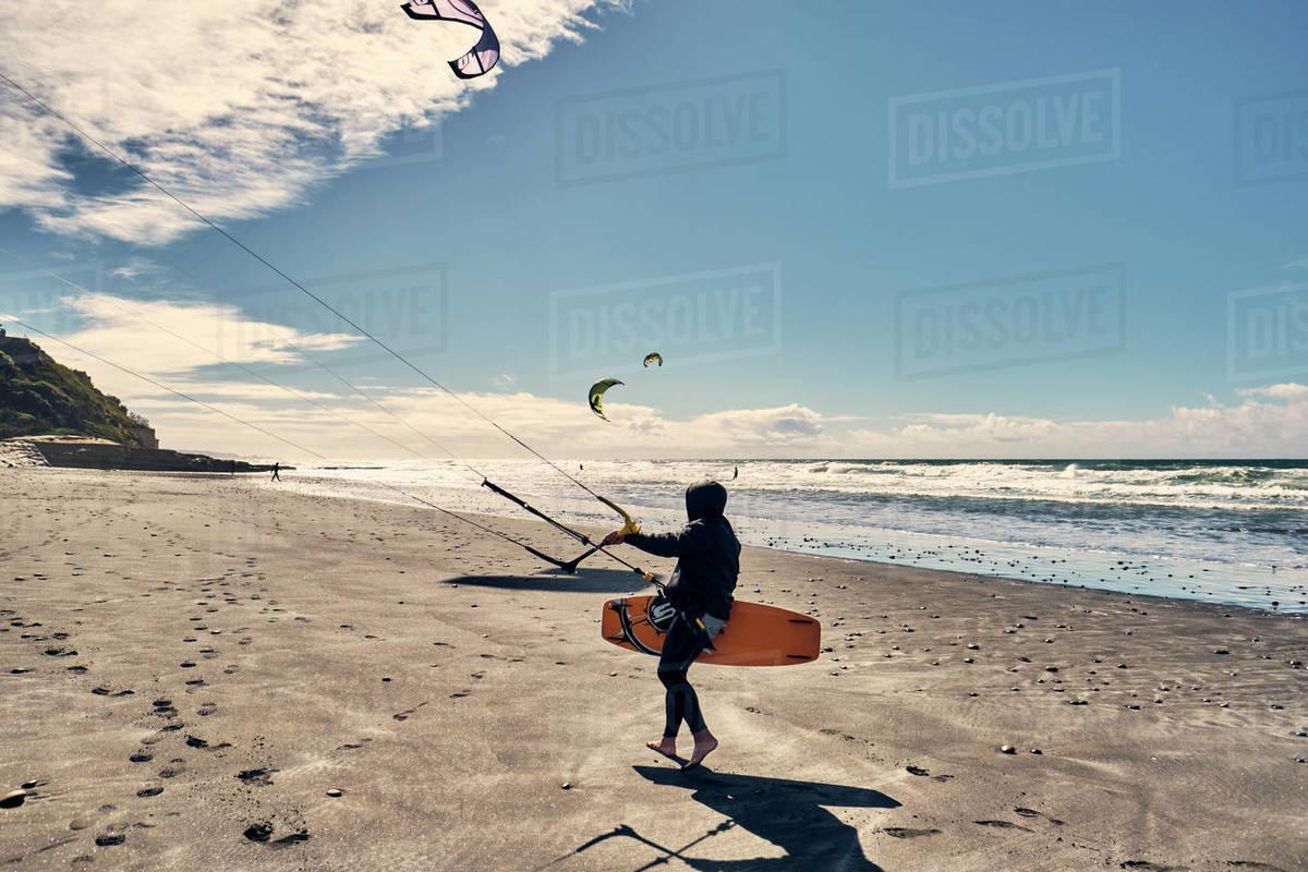 A kite surfer walks along a beach in Southern California, San Diego Royalty-free stock photo