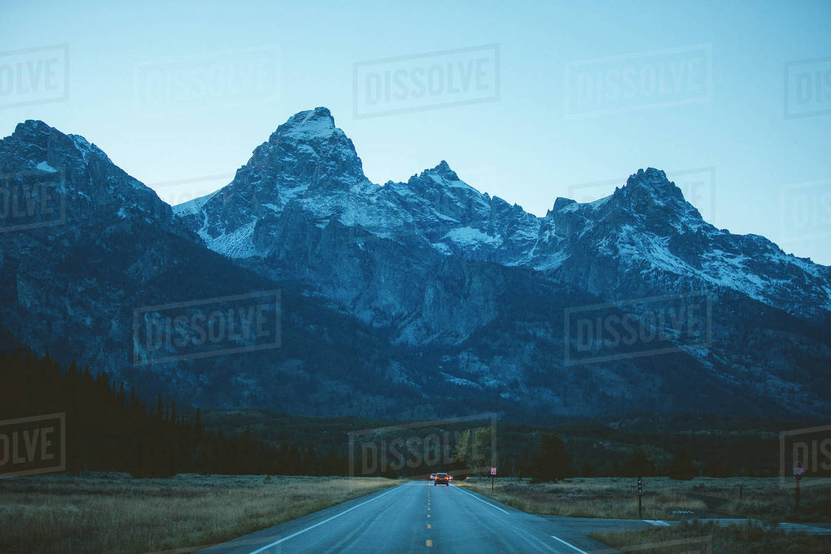 A pair of cars drive towards the Grand Teton mountain range at sunset. Royalty-free stock photo