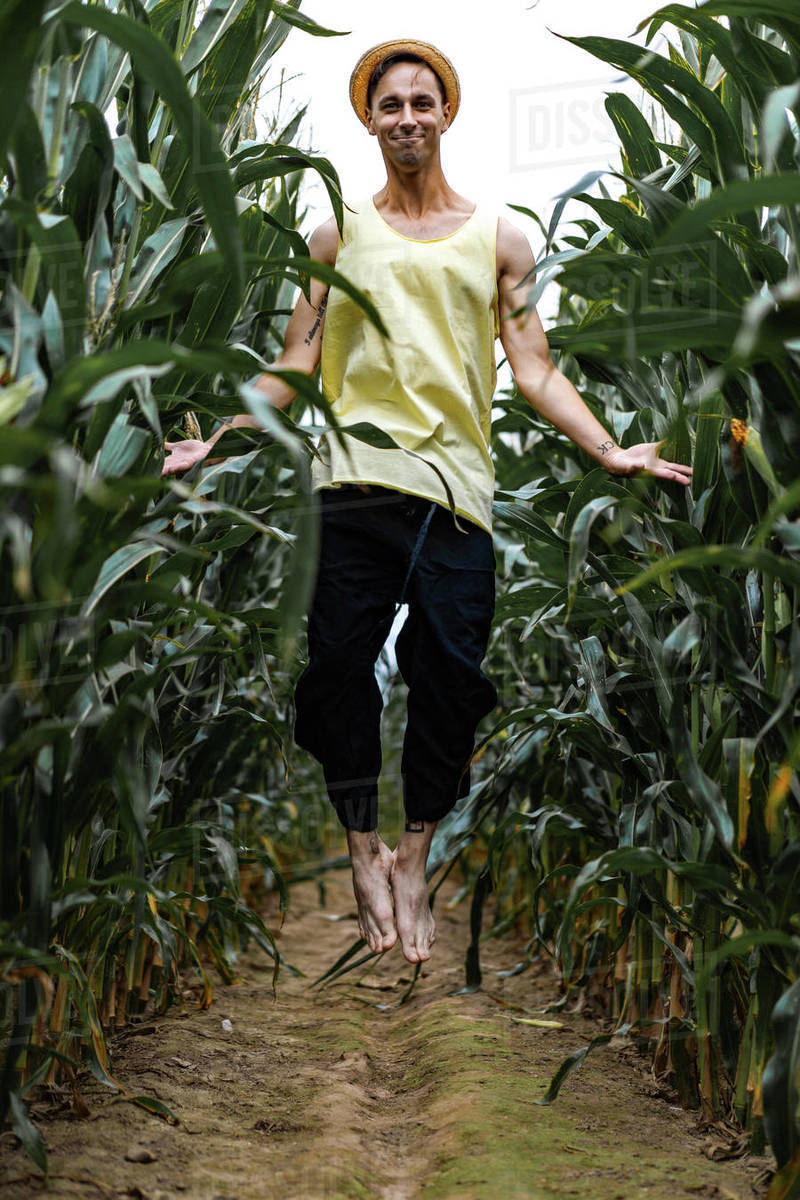 Farm man in a hat jumping and smiling in a green corn field. Royalty-free stock photo