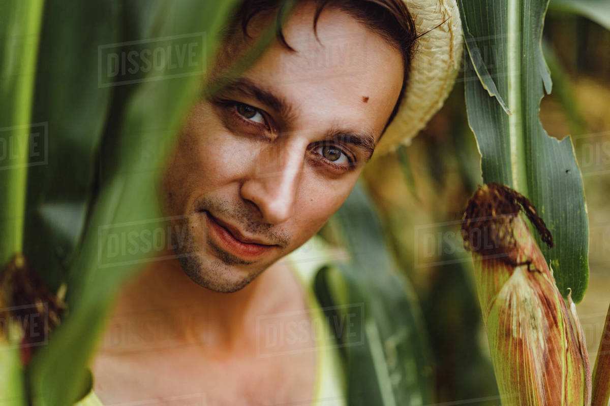 Portrait of a smiling farm man in a hat in a green field. Royalty-free stock photo
