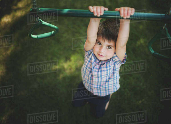 High angle portrait of boy hanging on monkey bars in playground Royalty-free stock photo