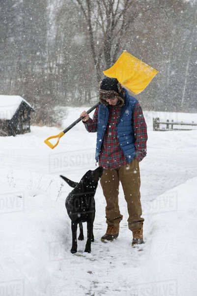 Man carrying shovel while standing with dog on snow covered field Royalty-free stock photo