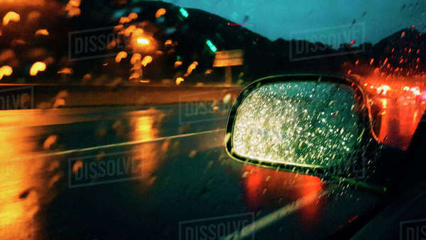 Side-view mirror seen through car window during rainy season at night Royalty-free stock photo