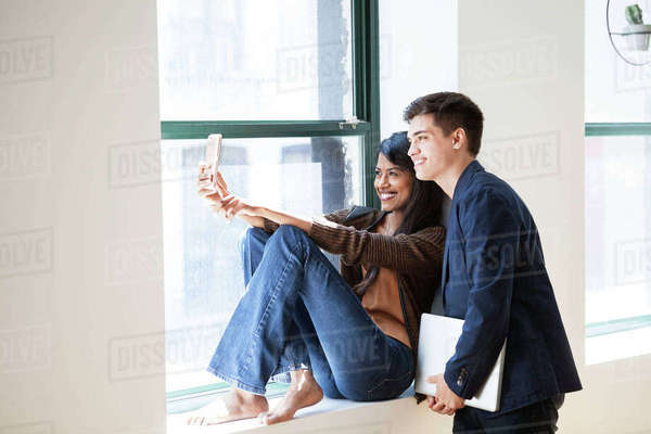 Happy business colleagues taking selfie through smart phone by window in creative office Royalty-free stock photo