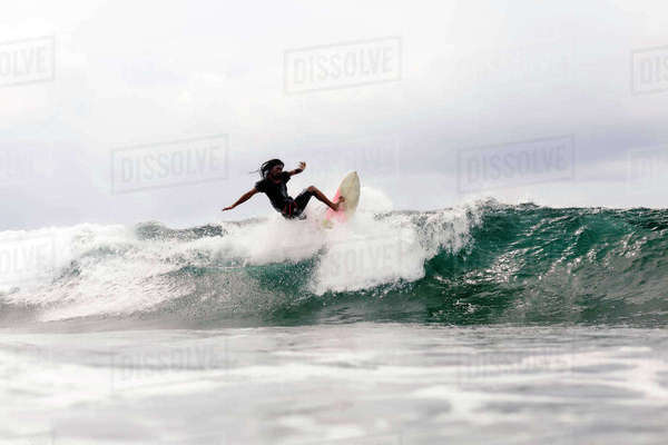 Man surfboarding on wave in sea against cloudy sky Royalty-free stock photo