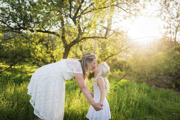 Side view of pregnant mother kissing daughter in park Royalty-free stock photo