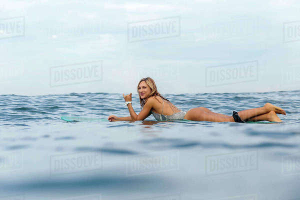 Portrait of smiling woman gesturing while surfing in sea against cloudy sky Royalty-free stock photo