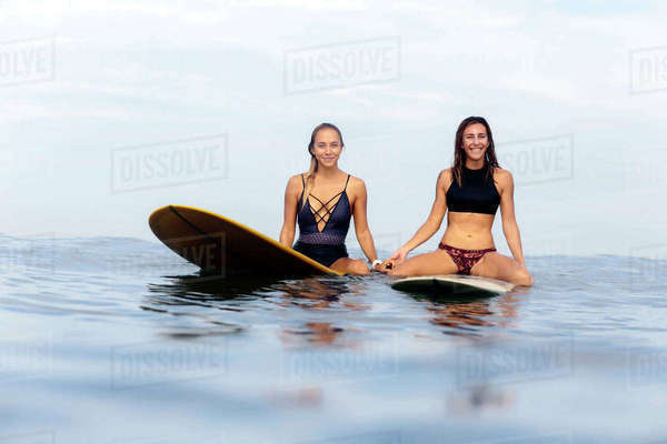 Portrait of female friends surfing on sea against cloudy sky Royalty-free stock photo