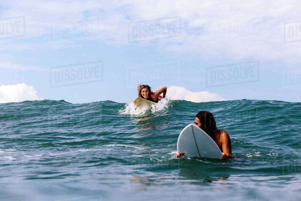 Happy friends surfing on sea against sky Royalty-free stock photo
