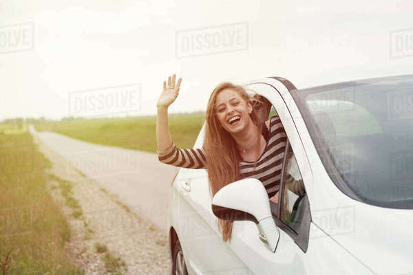 Cheerful young woman waving while peeking from car window on country road Royalty-free stock photo