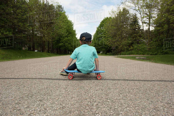 Rear view of boy sitting on skateboard at footpath Royalty-free stock photo