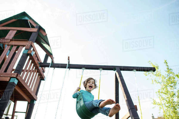Low angle portrait of girl swinging at playground Royalty-free stock photo